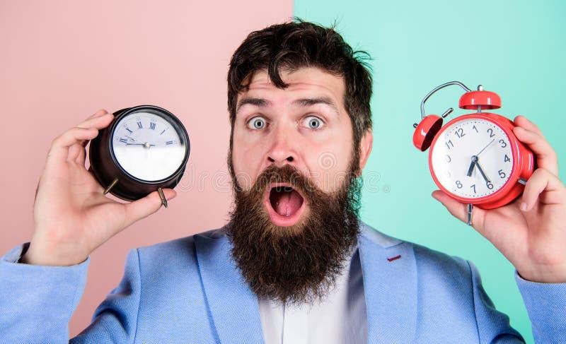 För hipsterhåll två för man skäggiga olika klockor Orakad förbryllad framsida för grabb som har problem med ändrande tid Tidszon arkivbilder