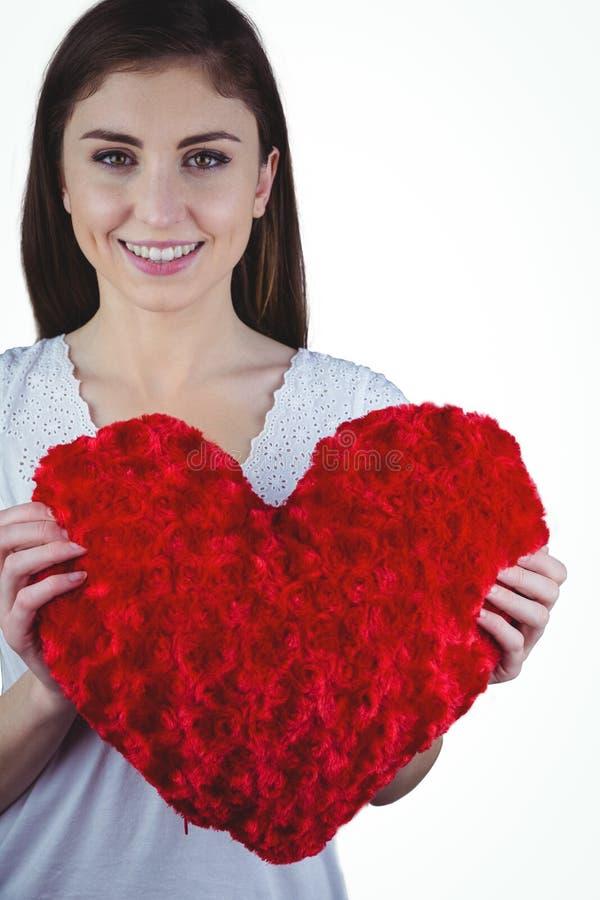 För hjärtaform för kvinna hållande kudde royaltyfria bilder