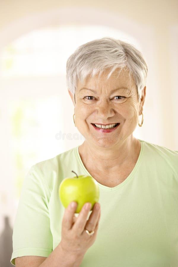 för holdingpensionär för äpple sund kvinna arkivbild
