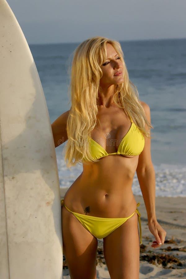 för holdingsurfingbräda för bikini blond kvinna arkivfoton