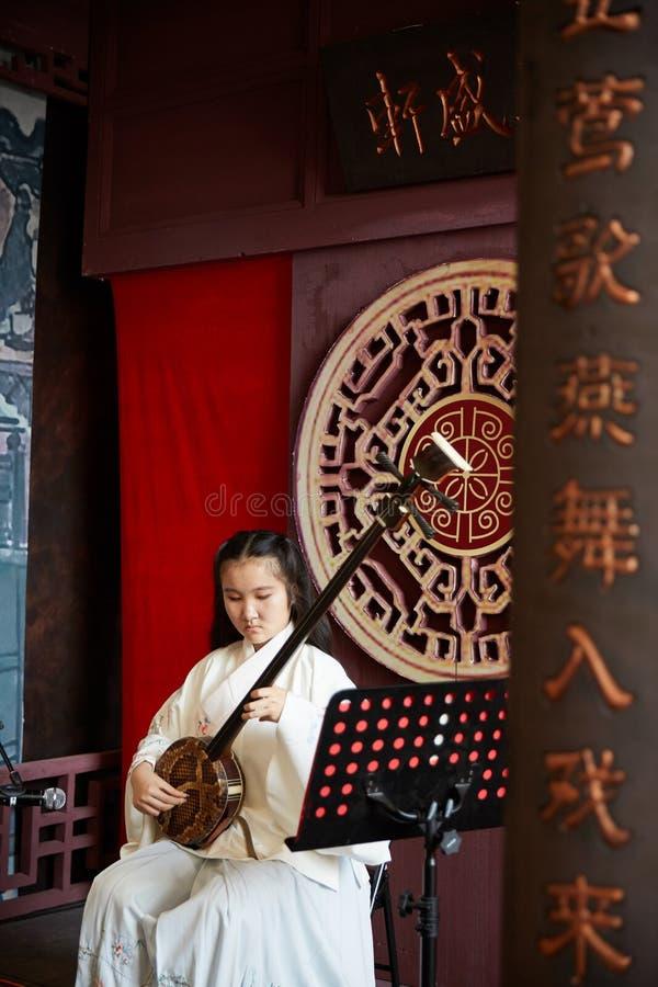 För Hu för kinesisk flicka utförande hm instrument musik royaltyfri bild