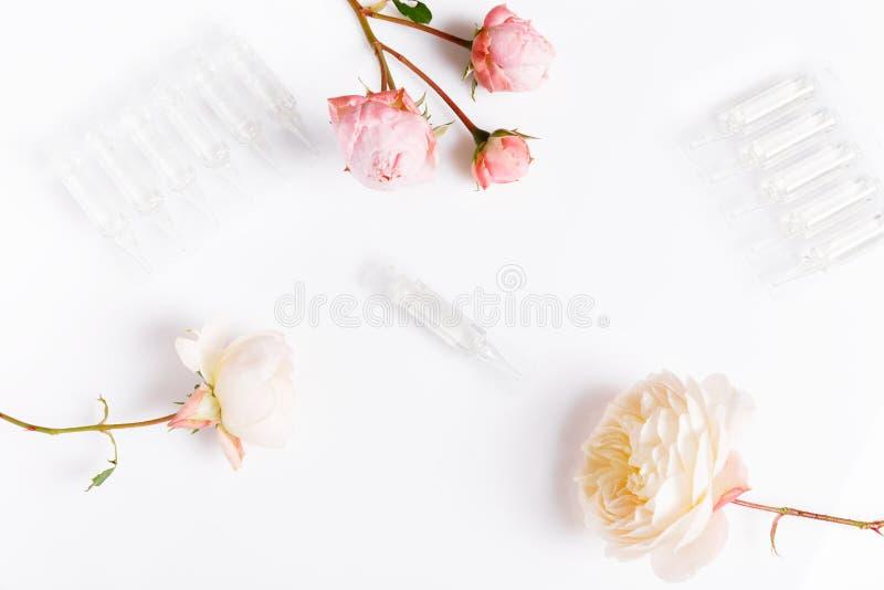 För hudomsorg för elit ansikts- produkt i ampull och rosor på vit bakgrund arkivbild