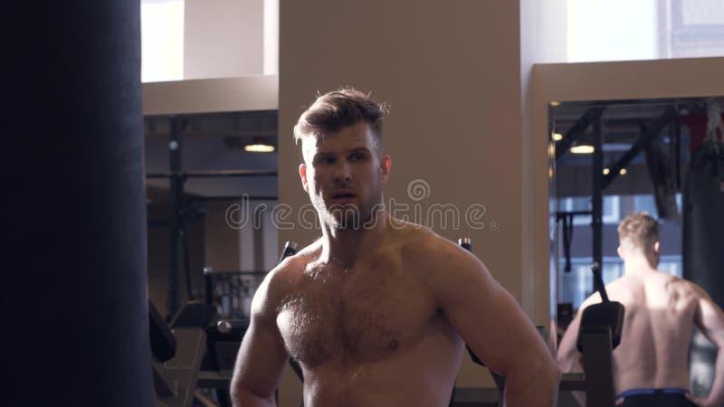 För idrottsman nenframdel för stående svettig spegel i konditionklubba Framsidamankroppsbyggare arkivfoto