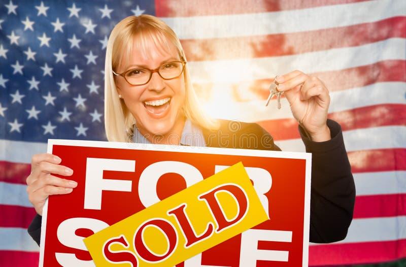 För innehavhus för ung kvinna tangenter och sålt tecken framme av amerikanska flaggan royaltyfria bilder