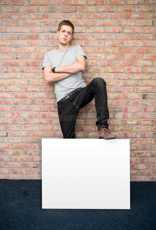 För innehavmellanrum för ung man whiteboard royaltyfri fotografi
