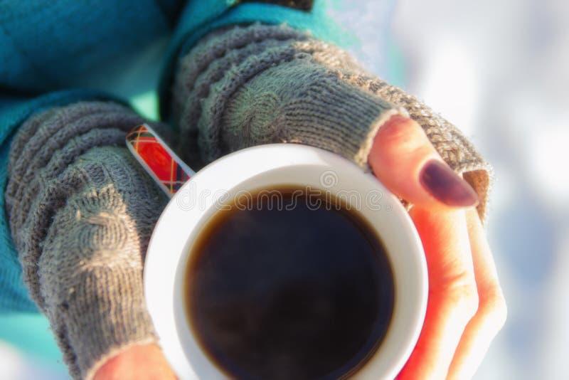 För innehavvinter för ung kvinna slut för kopp upp på snöbakgrund arkivbild
