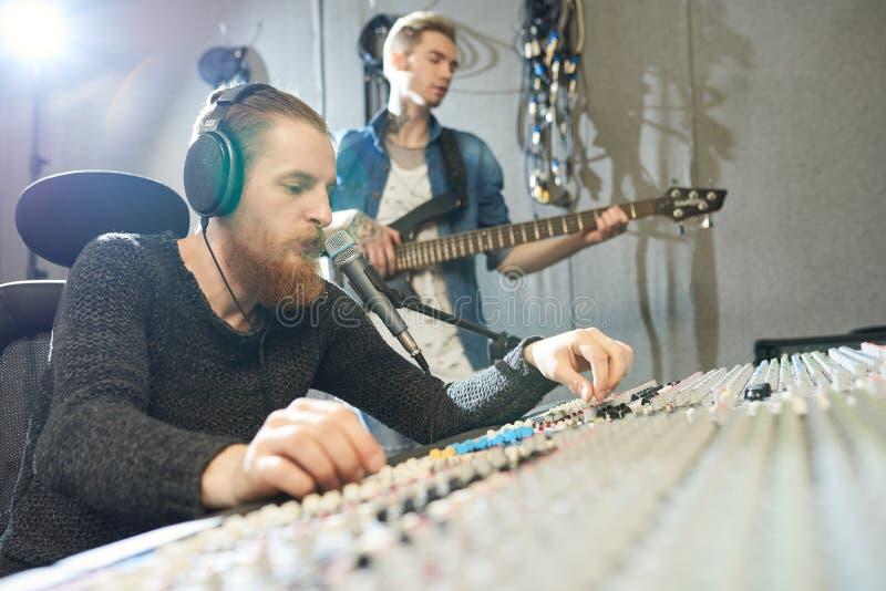För inspelninggitarr för solid tekniker kapacitet i studio arkivbilder
