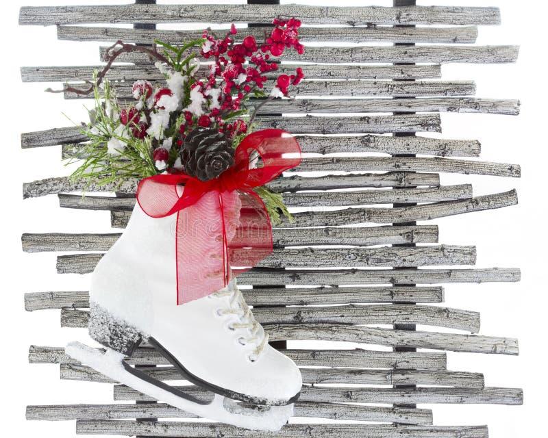 För isskridskon för jul sörjer det röda bandet för vita skor lantligt kotteträ royaltyfri foto