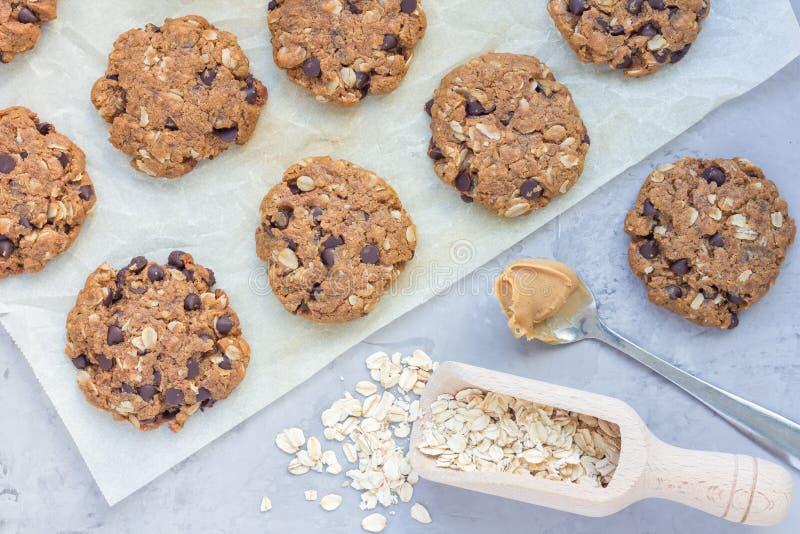 För jordnötsmör för Flourless gluten fria kakor för chiper, havremjöl- och chokladpå ett pergament, bästa sikt som är horisontal arkivfoton