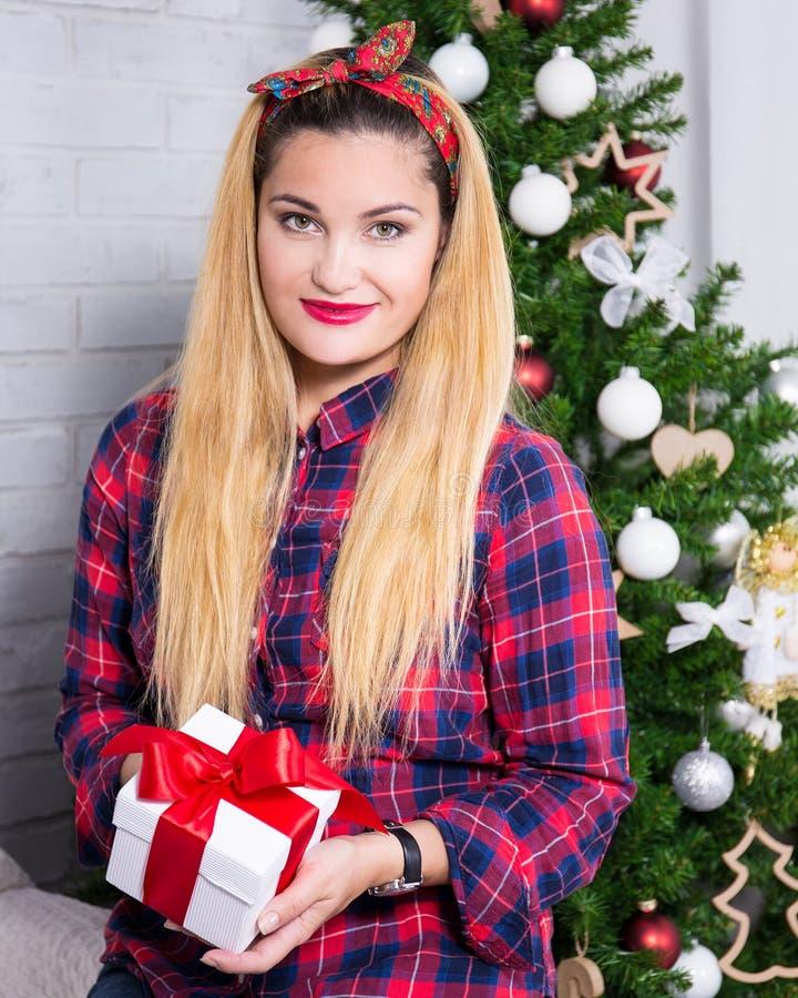För julgåva för ung härlig kvinna hållande ask, i dekorerat fotografering för bildbyråer