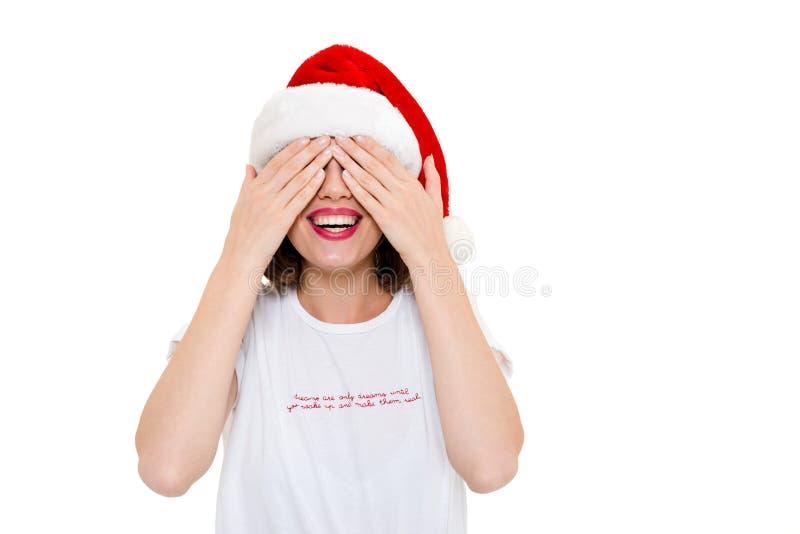 För julhatten för den nätta caucasian kvinnan synar bärande beläggning med händer royaltyfria bilder