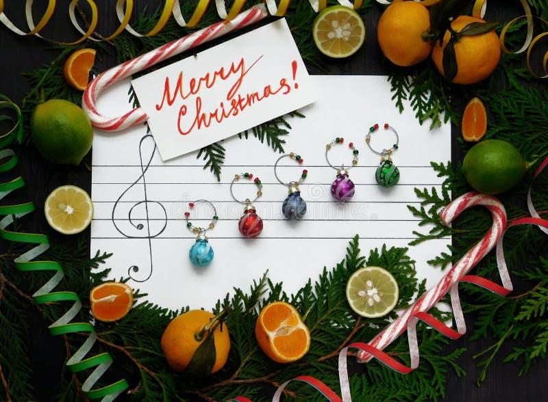 för julsammansättning för bauble blått exponeringsglas Julgarneringbollar är ordnade på papperet som musikanmärkningar arkivfoton