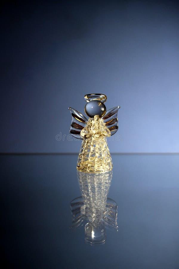 För julstaty för exponeringsglas genomskinlig ängel för leksak med förgyllda vinglekar på trumpetmusiken royaltyfria bilder