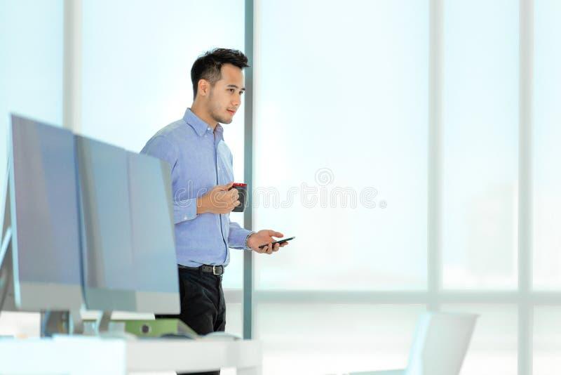 För för kaffekopp och smartphone för ung asiatisk affärsman hållande smilin royaltyfri fotografi