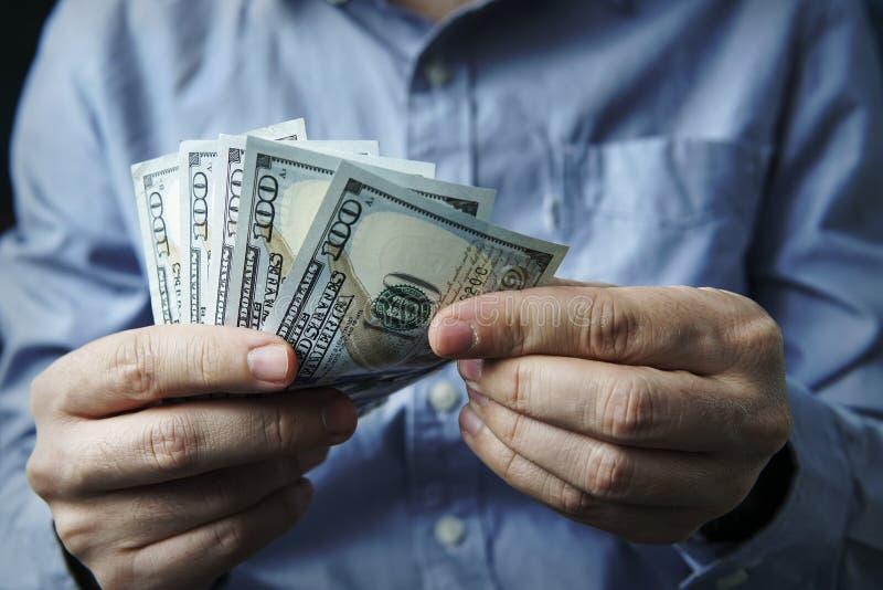 För kassa händer in Vinster besparingar Bunt av dollar arkivfoto
