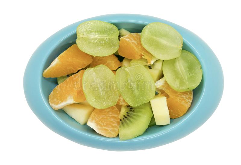 För kiwiäpplen för kärnfria druvor orange snitt i stycken i blått ovalt sh royaltyfri foto