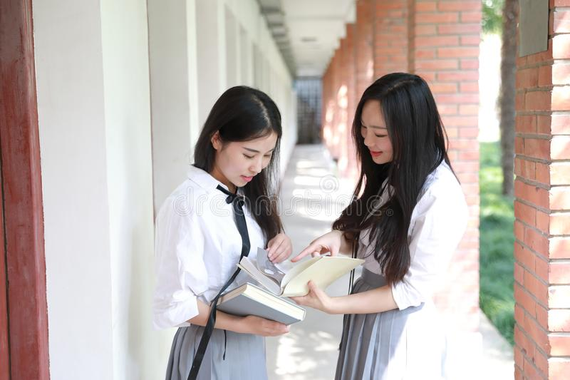 För kläderstudenten för två ler den älskvärda asiatiska kinesiska nätta flickor dräkten i skolabästa vän skrattläseboken i natur arkivbild