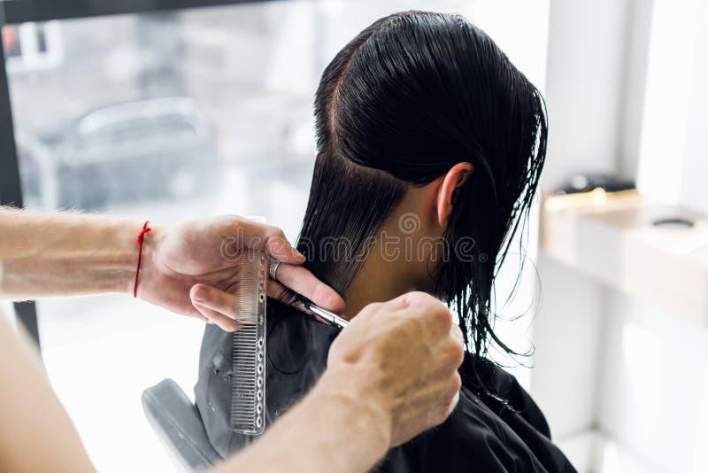 För klient` s för frisör bitande hår i salong med saxcloseupen Använda en hårkam royaltyfria bilder