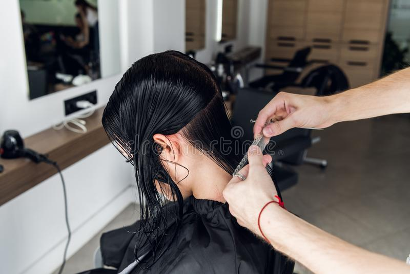 För klient` s för frisör bitande hår i salong med saxcloseupen Använda en hårkam arkivbilder