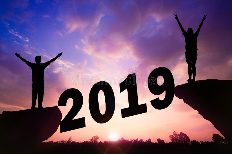 För kontursolnedgång för lyckligt nytt år bakgrund Ett man- och kvinnaanseende på klippan arkivbild