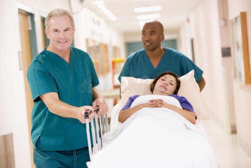 för korridor som sjukvårdare ner skjuter kvinna två royaltyfri bild