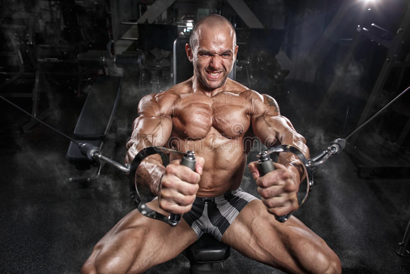 För kroppsbyggareutbildning för idrottsman nen muskulös bröstkorg på simulatorn i idrottshallen royaltyfria foton