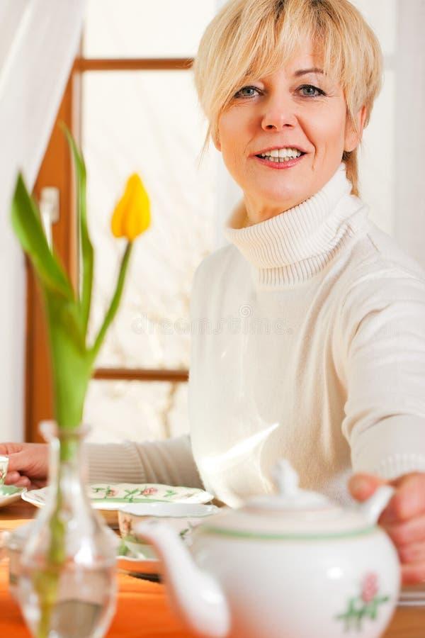 för krukatea för kaffe gripande kvinna royaltyfria bilder