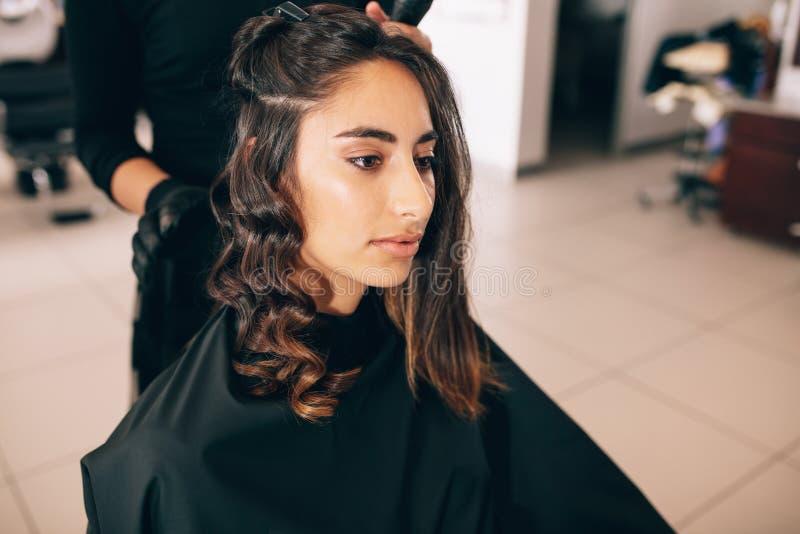 För kvinna` s för stylist krullande hår i skönhetsalong arkivbild
