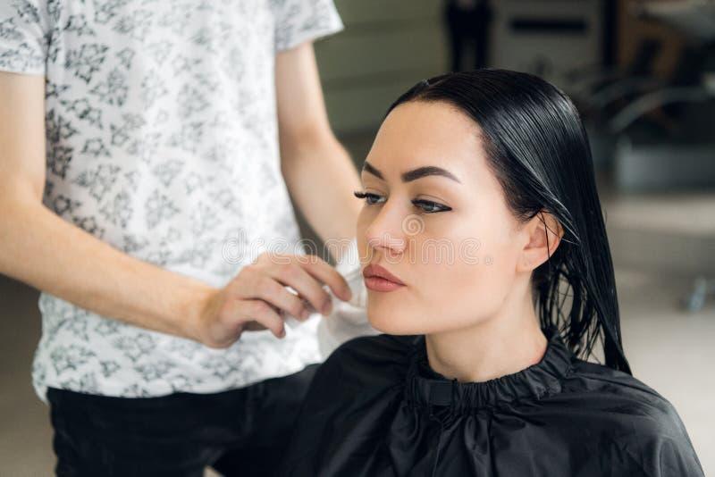 För kvinna` s för frisör bitande hår i salong och att le, främre sikt, närbild, stående arkivfoton