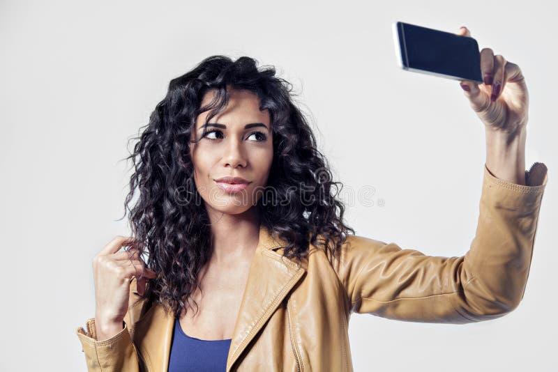 För kvinnadanande för Afroamerican svart sexigt foto för selfie Svart långt hår, läderomslag royaltyfria bilder