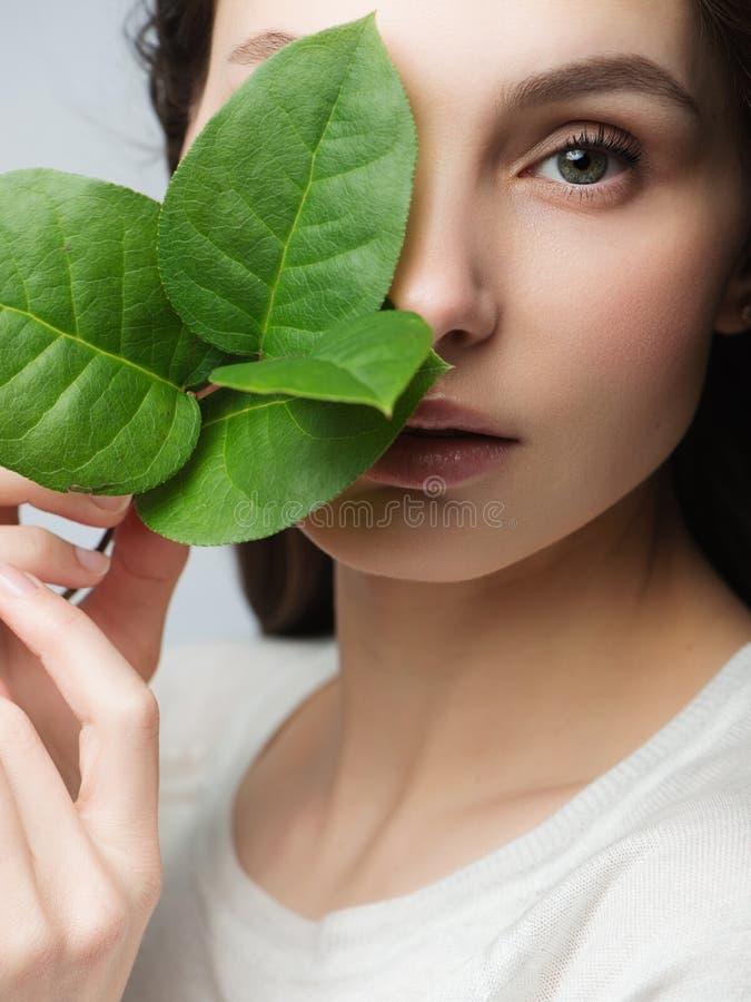 För kvinnaframsida för stående härlig stående med det gröna bladet, begreppet för hudomsorg eller organiska skönhetsmedel fotografering för bildbyråer