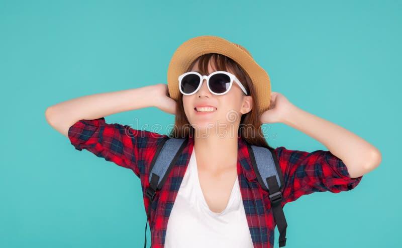 För kvinnakläder för härlig stående som tycker om det säkert unga asiatiska leendet för solglasögon och för hatten är u royaltyfri foto