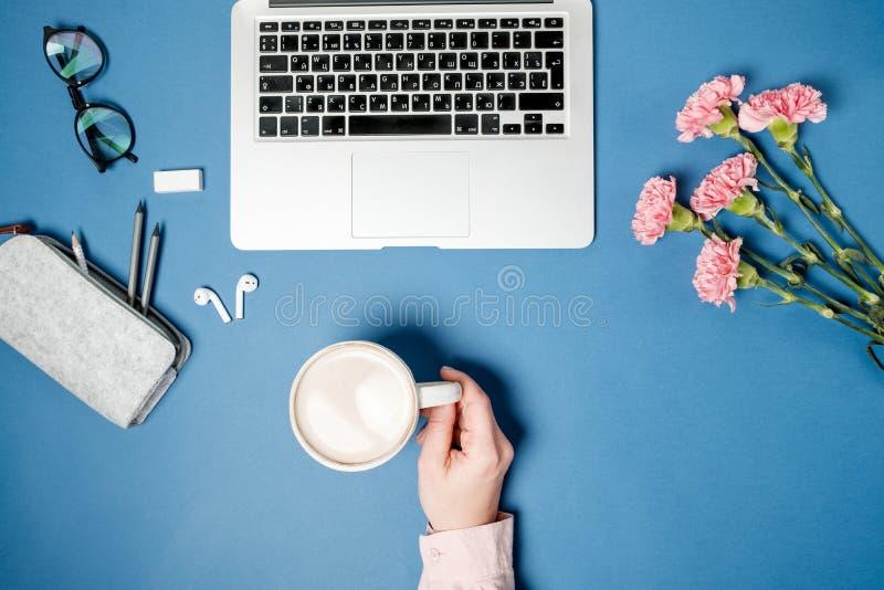 För kvinnakontor för lägenhet lekmanna- skrivbord Kvinnlighänder med kaffe och bärbara datorn, royaltyfri fotografi