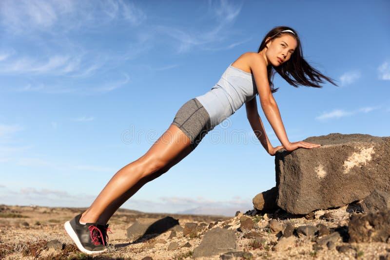 För kvinnaliggande armhävning för kondition som asiatisk planka utarbetar armar arkivfoton