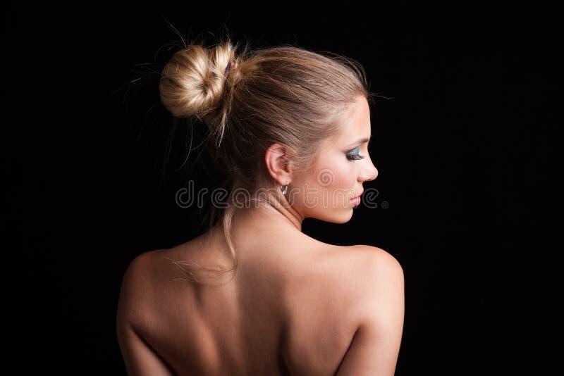 För kvinnastående för skönhet ungt blont hår i bulleprofil royaltyfri foto