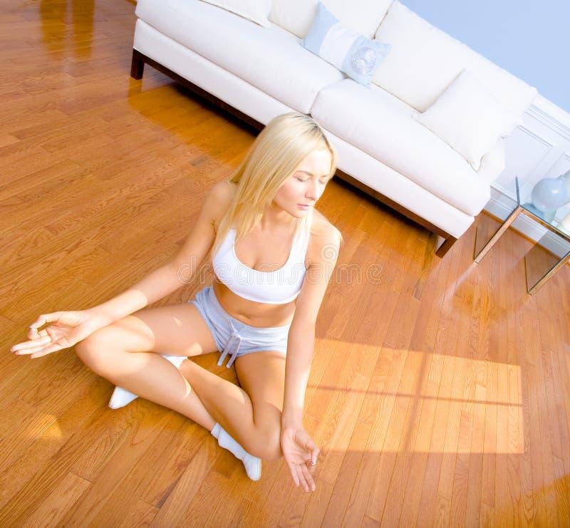 för kvinnaträ för golv meditera sittande barn arkivfoto