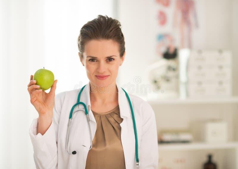 För kvinnavisning för medicinsk doktor äpple arkivfoto