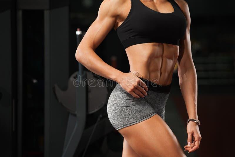 För kvinnavisning för kondition buktar sexiga abs och lägenheten i idrottshall Härlig idrotts- flicka, formad buk- slank midja arkivfoto