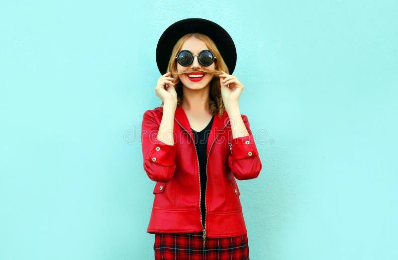 För kvinnavisning för stående rolig le mustasch hennes hår i den svarta runda hatten, rött omslag på blått royaltyfri foto