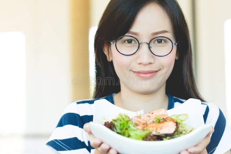 För kvinnavisning för sund livsstil asiatiskt le för sallad fotografering för bildbyråer