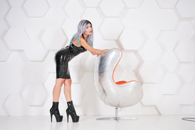 För latexgummi för varm sexuell kvinna bärande alternativ dräkt på futuristisk bakgrund för vit studio arkivbild