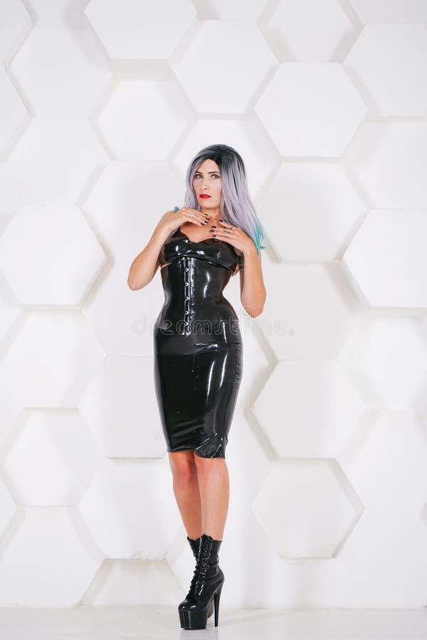 För latexgummi för varm sexuell kvinna bärande alternativ dräkt på futuristisk bakgrund för vit studio fotografering för bildbyråer
