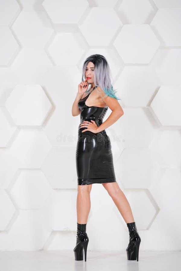 För latexgummi för varm sexuell kvinna bärande alternativ dräkt på futuristisk bakgrund för vit studio arkivfoton