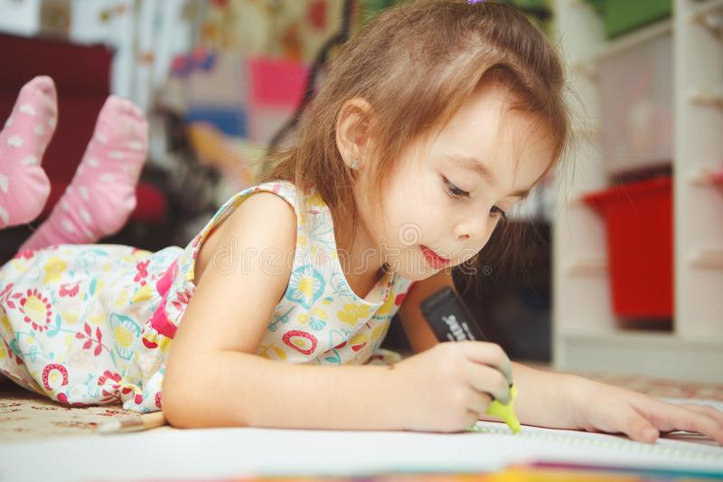 För liten flicka attraktionbild försiktigt i anteckningsbok med filtpennan arkivfoton