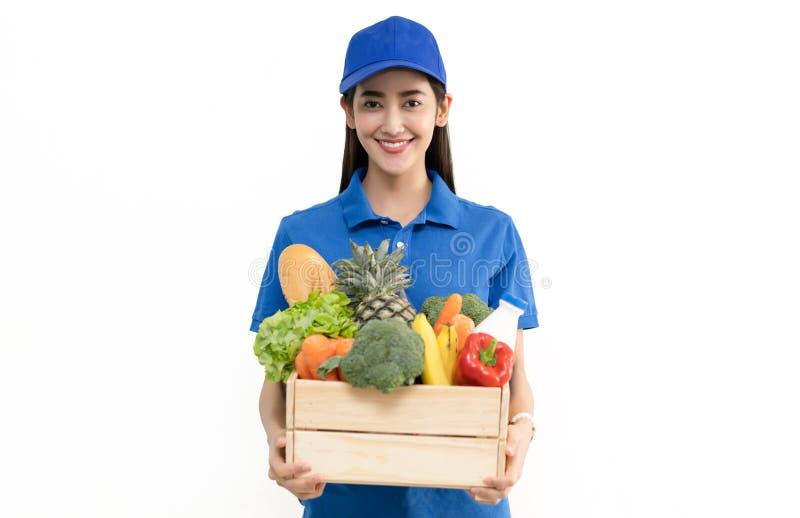 För livsmedelsbutikleverans för ung kvinna caucasian man för kurir i blå likformig med livsmedelsbutikträasken med den nya frukt  arkivbilder