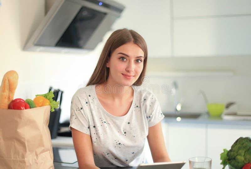 För livsmedelsbutikshopping för ung kvinna hållande påse med grönsaker som står i köket arkivfoton