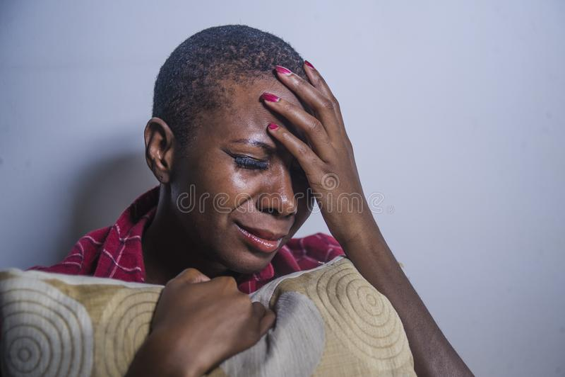 För livsstil stående inomhus av den unga ledsna och deprimerade svarta afro amerikanska kvinnan som sitter hemmastadd desperat go royaltyfri bild