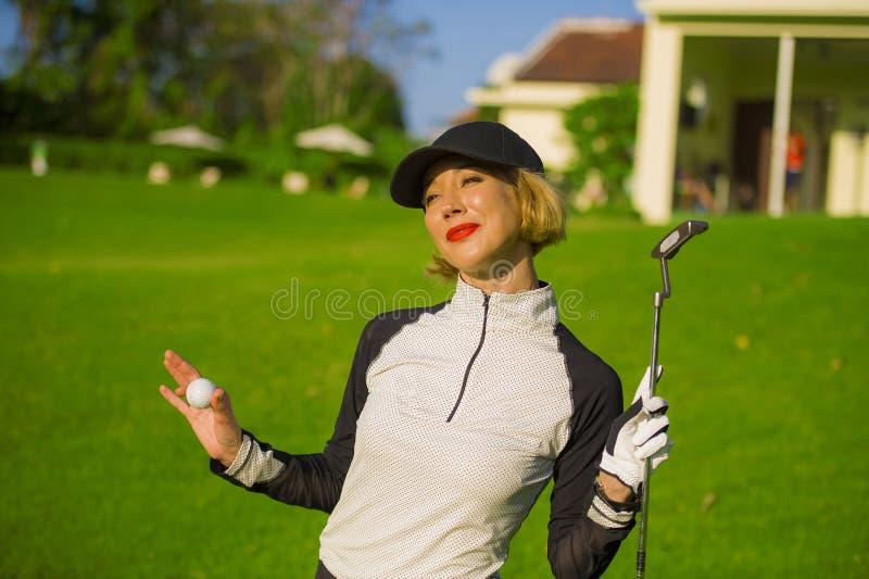 För livsstil stående utomhus av den unga härliga och lyckliga kvinnan på att spela att le för klubba för för golfinnehavboll som  royaltyfri fotografi