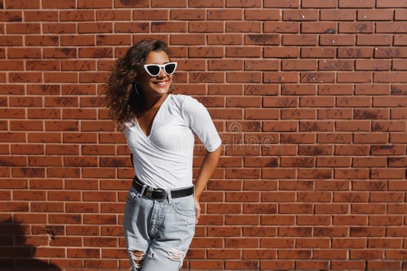 För livsstilmode för sommar solig stående av den unga stilfulla hipsterkvinnan med den lockiga flickan för brunett arkivfoto