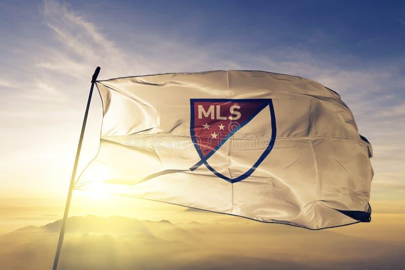 För logoflagga för MLS som Major League Soccer tyg för torkduk för textil vinkar på den bästa soluppgångmistdimman stock illustrationer